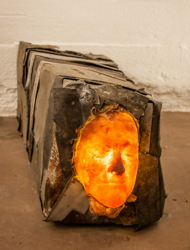 the sculpture shows a mysterious face connected with a body made of metal. illuminated from the inside
